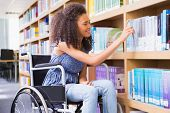 pic of disability  - Smiling disabled student in library picking book at the university - JPG