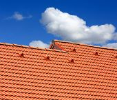 stock photo of red roof  - Abstract red tiled roof on blue sky background - JPG