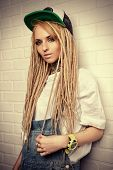 picture of dreadlocks  - Modern teenage girl with blonde dreadlocks standing by the brick wall - JPG