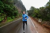 ������, ������: Male runner jogging and running on road in rain in jacket and long tights Fit fitness model man wor