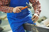 stock photo of chisel  - carpenter installer works with hammer and chisel at interior wood door installation - JPG