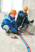 stock photo of floor heating  - two repairman engineer installing house floor heating system at interior construction site - JPG