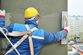 foto of putty  - builder at facade plastering work during industrial building with putty knife float - JPG