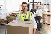 stock photo of warehouse  - Smiling warehouse worker carrying box in warehouse - JPG
