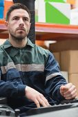 stock photo of forklift driver  - Portrait of focused driver operating forklift machine in warehouse - JPG