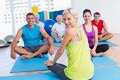 image of senior class  - Portrait of female instructor with class practicing yoga in fitness studio - JPG