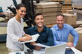 picture of warehouse  - Smiling warehouse managers working together in a large warehouse - JPG