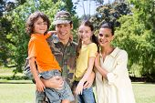 image of reunited  - Handsome soldier reunited with family on a sunny day - JPG