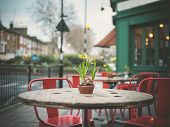 pic of lillies  - A table decorated with lillies outside a cafe in the street on a winter - JPG