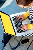 pic of sitting a bench  - Woman typing on laptop with empty yellow screen sitting on the bench  - JPG