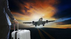 picture of running-late  - young business man and luggage suitcase standing with passenger plane take off from runways against beautiful dusky sky with copy space use for air transport journey and traveling industry business  - JPG