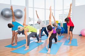 picture of senior class  - Full length of fit men and women doing stretching exercise at fitness club - JPG