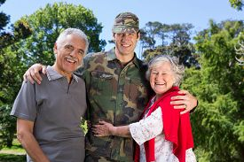 stock photo of reunited  - Soldier reunited with his parents on a sunny day - JPG
