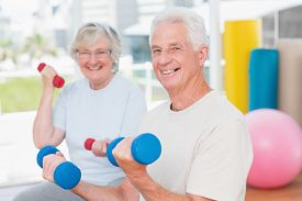 foto of senior class  - Portrait of happy senior couple lifting dumbbells in gym - JPG