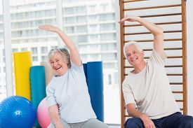 stock photo of senior class  - Portrait of happy senior couple doing stretching exercise in gym - JPG