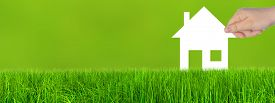 foto of ecology  - Concept or conceptual white paper house symbol held in hand by a woman in green summer grass background - JPG