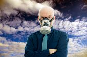 pic of gas mask  - young businessman with gas mask in front of cloudy sky - JPG
