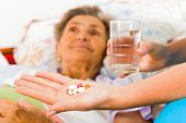 foto of nurse  - Nurse giving medication to elderly patient in nursing home - JPG