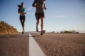 pic of angle  - Low angle shot of young woman running on road with man in front on a summer morning - JPG