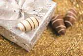 image of gift wrapped  - Close up of a gift pack wrapped in a silver paper along with three date - JPG