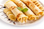 image of crepes  - Crepes with bananas and cream on white background  - JPG