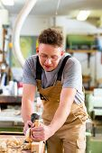 image of carpentry  - Carpenter working with a wood planer on workpiece in his workshop or carpentry - JPG