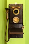 stock photo of rotary dial telephone  - old classic wood telephone hanging on green wall - JPG