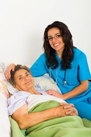 stock photo of nursing  - Nurse caring for sick elder lady in nursing home - JPG