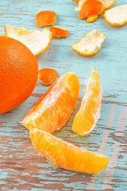 pic of mandarin orange  - Fresh Ripe Sweet Orange Tropical Fruit Sliced Sections and Peel on Rustic Grunge Blue Wood Background - JPG