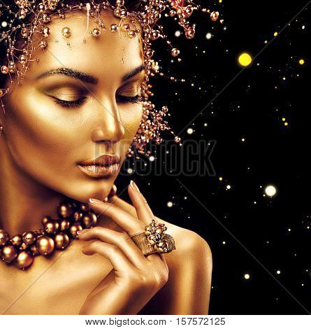 Beauty Fashion model girl with Golden Makeup, Gold skin makeup, hair and jewellery on black backgrou