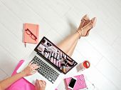Woman watching online tutorial on laptop. Makeup and beauty blog. poster