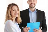 Businessman consulting young woman in office poster