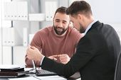 Businessman consulting young man in office poster