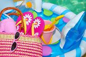 pic of floaties  - Pool toys and accessories on deck next to pretty pool water - JPG