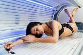 A Slender Brunette Girl Lies In A Horizontal Tanning Salon, Wants A Beautiful Even Tan poster