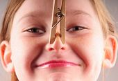Young girl with clothespin on nose
