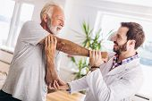 Man Having Chiropractic Arm Adjustment. Physiotherapy, Sport Injury Rehabilitation. Senior Man Exerc poster