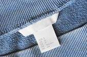 Small Size Clothes Label On Blue Textile Background Closeup poster