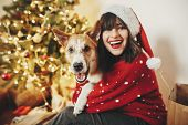 Happy Girl In Santa Hat Hugging With Cute Dog On Background Of Golden Beautiful Christmas Tree With  poster