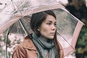 Autumn rainy grey day sad girl pensive. Asian woman in depression during fall season mood change. poster