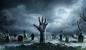 Zombie Hand Rising Out Of A Graveyard In Spooky Night poster