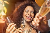 Happy young african woman holding wine glass with friends at party. Portrait of beautiful black girl poster