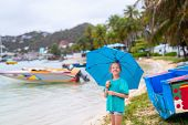 Happy little girl with big blue umbrella outdoors at beach on rainy day poster