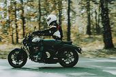 Biker In Helmet Is Riding On Highway In A Forest. Speed Vehicle. Cool Rider With A Leather Jacket. M poster
