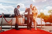 Couple arriving with limousine walking red carpet, a driver is opening the car door poster