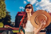 Young Stylish Woman In Sunglasses Holding Hat Outdoors. Stylish Girl Waving With Hat Resting On Benc poster