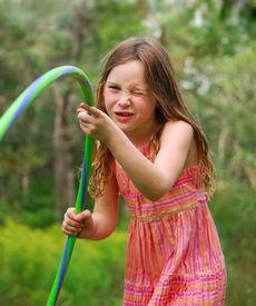 stock photo of hulahoop  - Young girl playing with hula hoop outside - JPG