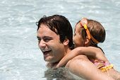 stock photo of swimming pool family  - Father playing with his daughter in swimming pool - JPG