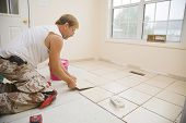 image of grout  - Man installing ceramic tile in customers kitchen getting ready to sell home
