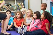 stock photo of pupils  - Elementary Pupils In Classroom Working With Teacher - JPG